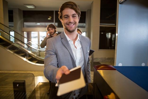 Homme d'affaires remettant sa carte d'embarquement au comptoir