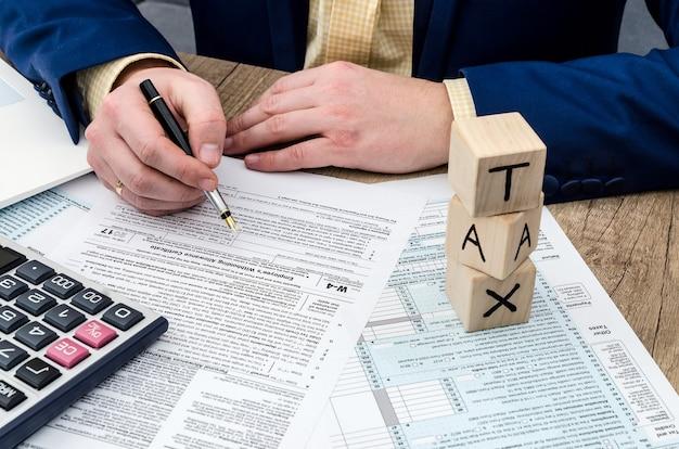 Homme d'affaires remplissant le formulaire w-4 avec stylo, calculatrice et pc