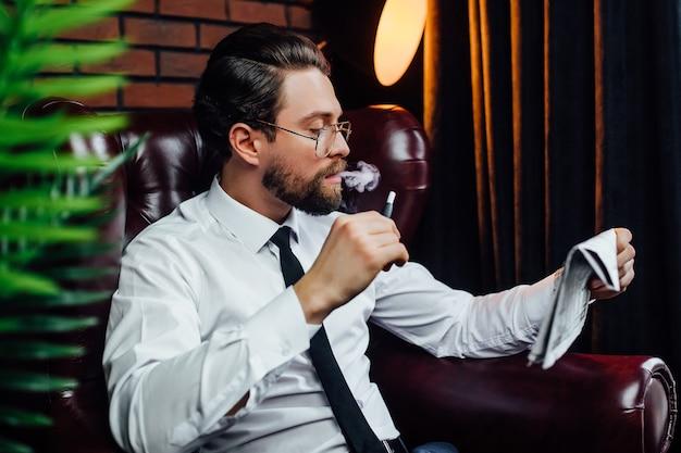 Homme d'affaires reposant sur un fauteuil dans une chambre de luxe. bel homme fumant un cigare dans sa maison.