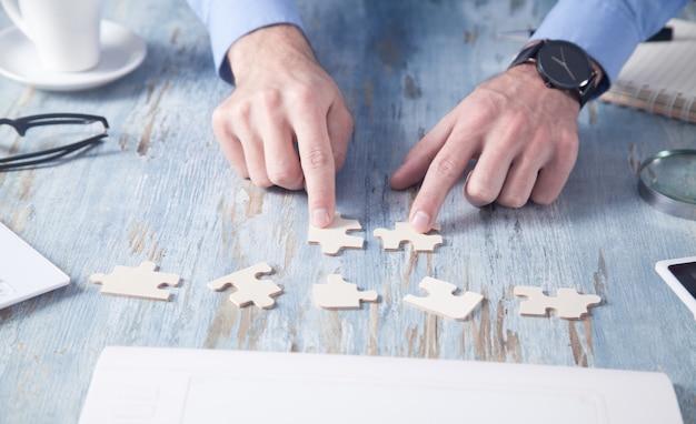 Homme d'affaires résolvant le puzzle au bureau.