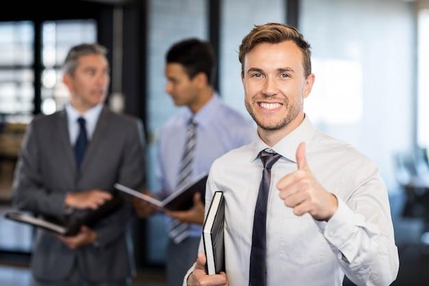 Homme d'affaires réussi levant son pouce tout en célébrant la victoire au bureau