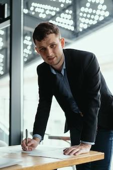 Homme d'affaires réussi, signature de documents dans un bureau moderne