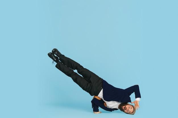 Homme d'affaires s'amusant à danser le break dance sur fond bleu au travail
