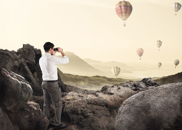 Homme d'affaires s'appuyant sur un rocher en regardant des montgolfières dans le ciel avec des jumelles