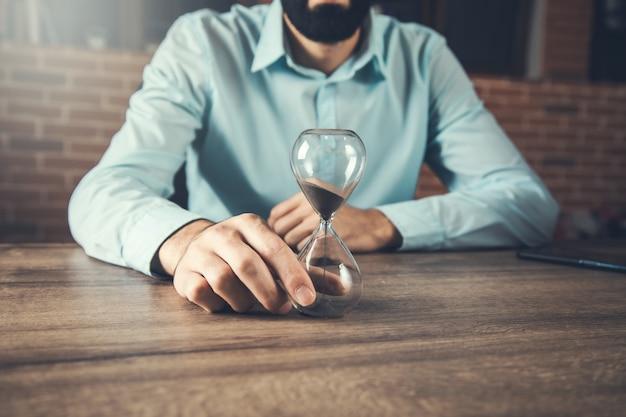 Homme d'affaires avec sablier sur le bureau en bois