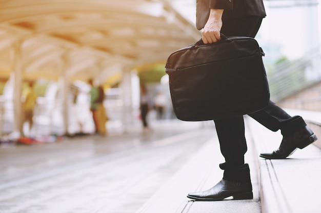 Homme d'affaires avec sac à la main en descendant les marches