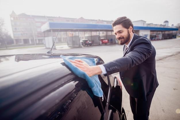 Homme d'affaires satisfait polissant sa voiture chère devant un lave-auto.