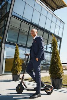 Homme d'affaires avec scooter électrique debout devant le bâtiment des entreprises modernes, parler au téléphone.