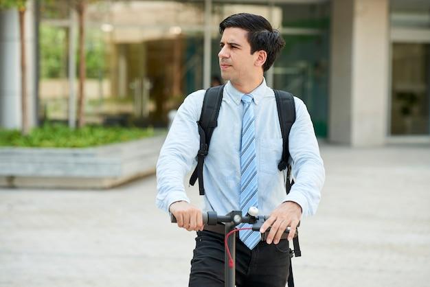 Homme d'affaires avec scooter à l'extérieur