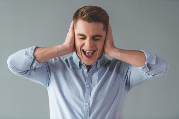 Homme d'affaires se couvre les oreilles et crie