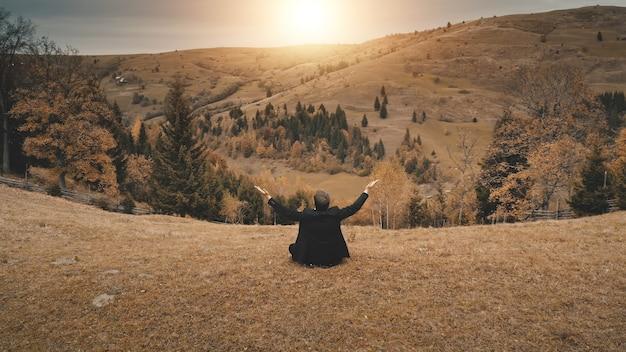 L'homme d'affaires se lève les mains au soleil montagne aérienne loisirs ruraux à la nature campagne de la forêt de pins