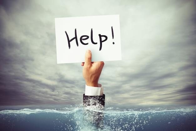 Homme d'affaires se noyant dans la mer avec une main tenant une feuille de papier avec l'aide écrite