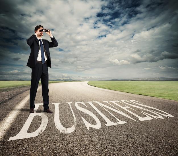 Homme d'affaires se penche sur l'avenir économique avec des jumelles sur la route des affaires