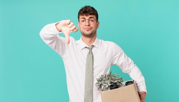 Homme d'affaires se sentant fâché, en colère, agacé, déçu ou mécontent, montrant les pouces vers le bas avec un regard sérieux. notion de licenciement