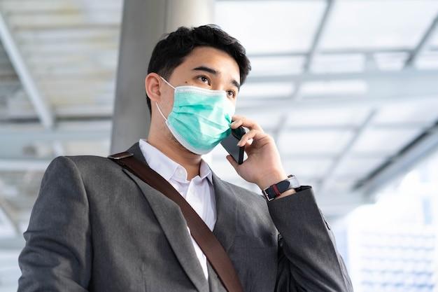 L'homme d'affaires se tient à l'extérieur et porte un masque tout en utilisant un téléphone portable