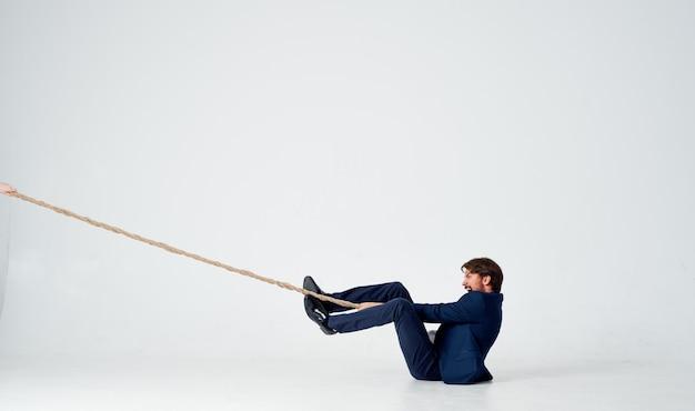 Un homme d'affaires se trouve sur le sol et tire une corde sur une lumière à l'intérieur