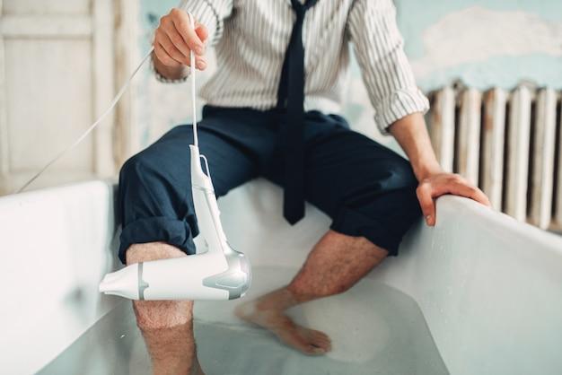 Homme d'affaires avec sèche-cheveux dans la baignoire, homme suicide