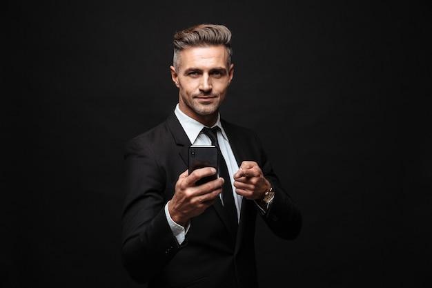 Homme D'affaires Séduisant Et Confiant Portant Un Costume Debout Isolé Sur Un Mur Noir, Utilisant Un Téléphone Portable, Célébrant Le Succès Photo Premium