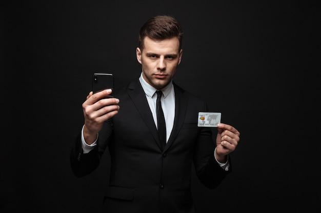 Homme d'affaires séduisant et confiant portant un costume debout isolé sur un mur noir, utilisant un téléphone portable, montrant une carte de crédit en plastique