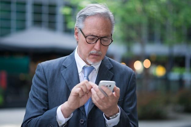 Homme d'affaires senior à l'aide de son téléphone portable à l'extérieur