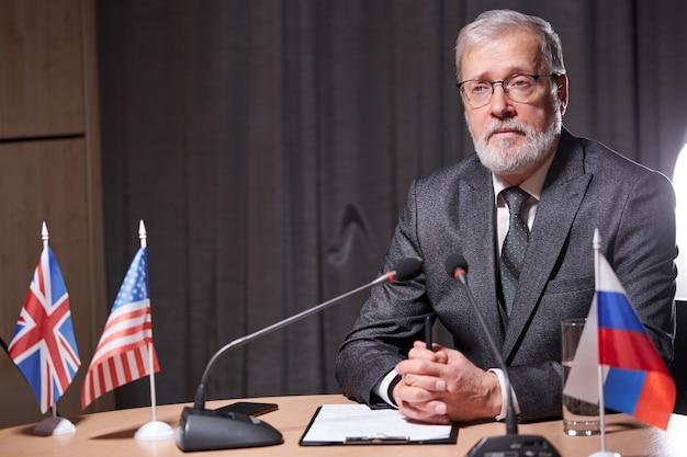 Homme d'affaires senior assis avec microphone dans la salle de conférence moderne lors de la réunion avec les partenaires commerciaux, beau homme à lunettes assis en toute confiance, portant un costume formel
