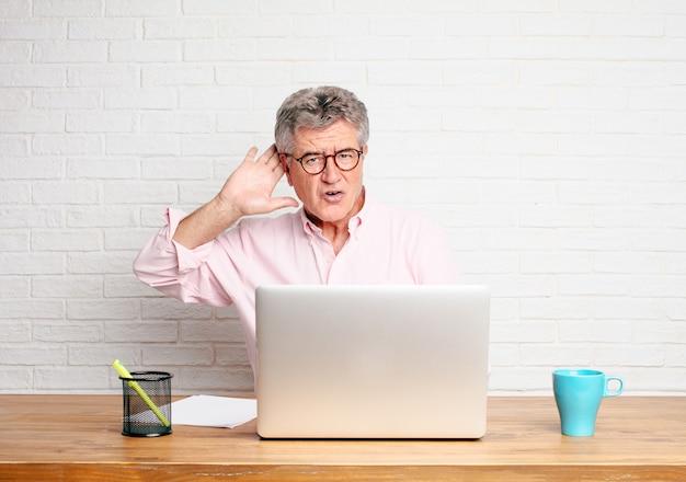 Homme d'affaires senior, attentif, essayant d'entendre