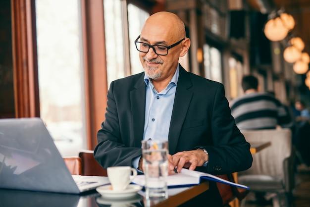 Homme d'affaires senior barbu regardant un ordinateur portable et écrivant des tâches dans l'ordre du jour tout en étant assis dans la cafétéria.