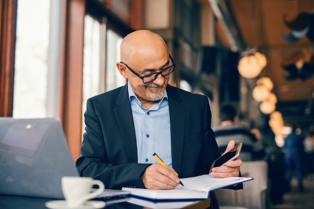 Homme d'affaires senior barbu regardant téléphone intelligent et tâches d'écriture dans l'ordre du jour tout en étant assis dans la cafétéria.