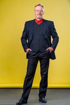 Homme d'affaires senior confiant souriant dans un costume sombre. les mains droites. t-shirt rouge. sur de soi. concept de style d'affaires