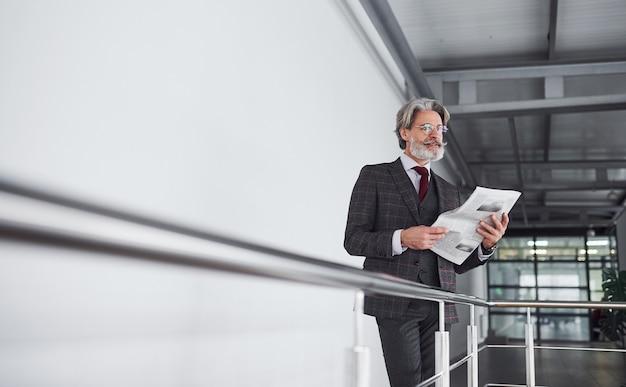 Homme d'affaires senior en costume-cravate aux cheveux gris et à la barbe tient des documents dans les mains.