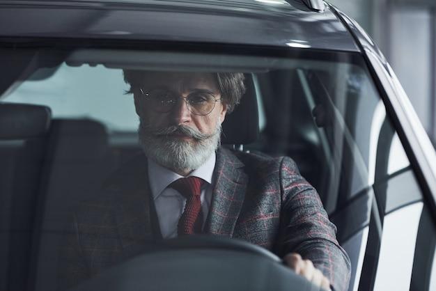 Homme d'affaires senior en costume-cravate avec cheveux gris et barbe conduisant la voiture.