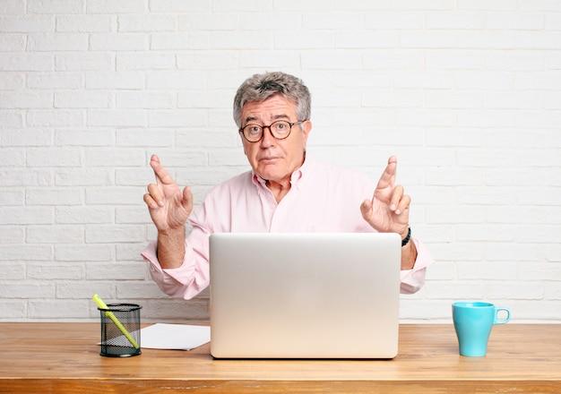 Homme d'affaires senior croise les doigts en quête de chance, avec une expression pleine d'espoir, empressée et excitée.