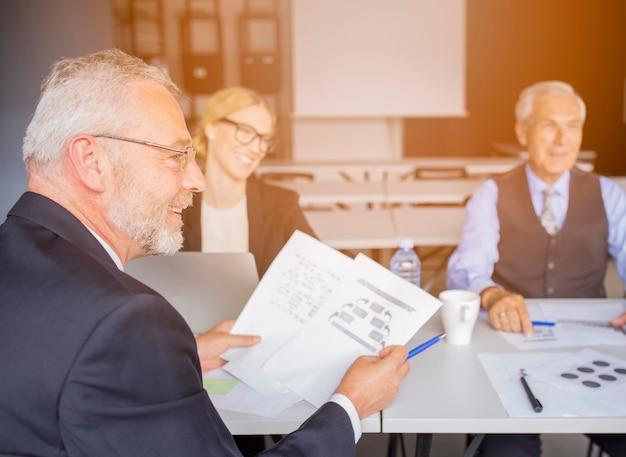 Homme d'affaires senior discutant du papier avec son collègue au bureau