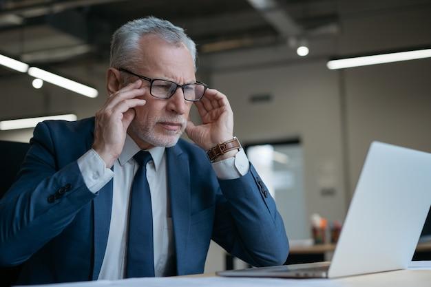 Homme d'affaires senior frustré à l'aide d'un ordinateur portable lisant des nouvelles travaillant au bureau