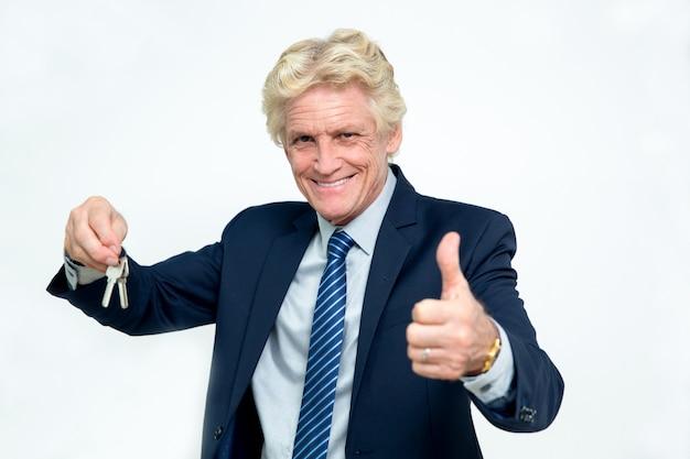 Homme d'affaires senior heureux montrant keys et thumb up