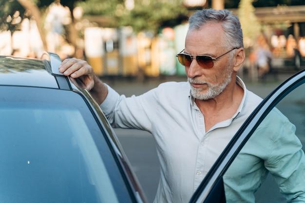 Homme d'affaires senior monte dans sa voiture après une dure journée de travail