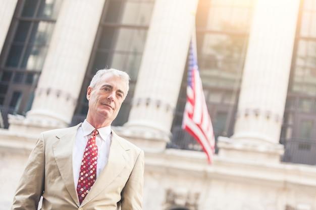 Homme d'affaires senior à new york avec drapeau américain