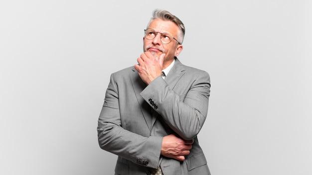 Homme d'affaires senior pensant, se sentant dubitatif et confus, avec différentes options, se demandant quelle décision prendre
