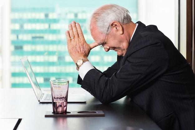 Homme d'affaires senior avec les pouces sur le front