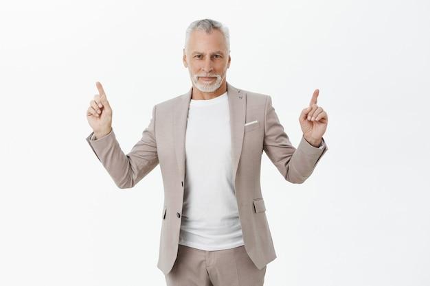 Homme d'affaires senior prospère en costume pointant les doigts vers le haut et souriant heureux