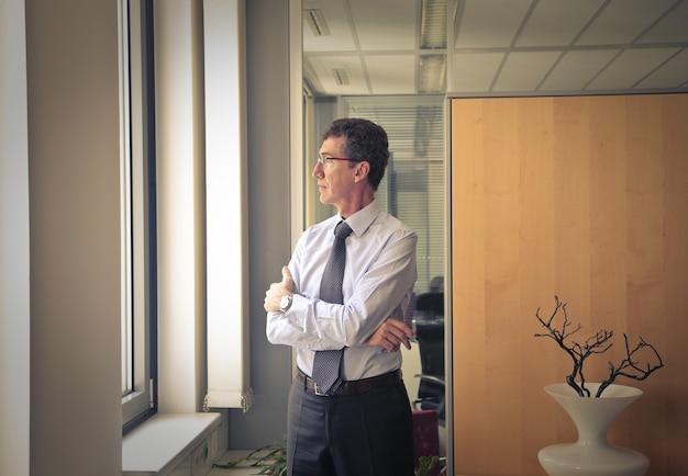 Homme d'affaires senior regardant par la fenêtre