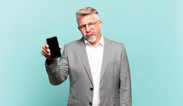 Homme d'affaires senior se sentant perplexe et confus, avec une expression stupide et abasourdie en regardant quelque chose d'inattendu