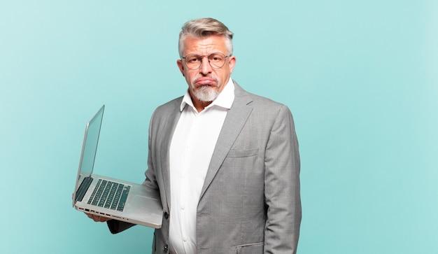 Homme d'affaires senior se sentant triste et pleurnichard avec un regard malheureux, pleurant avec une attitude négative et frustrée