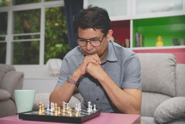 Homme d'affaires senior sérieux jouant au jeu d'échecs suppose de faire un plan de gestion de stratégie d'entreprise