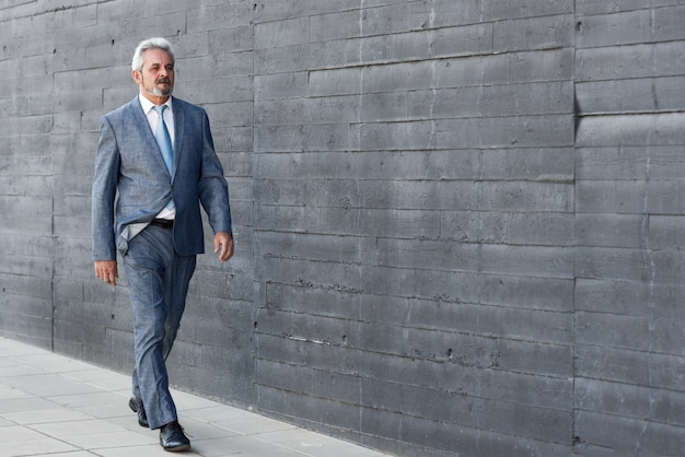 Un homme d'affaires senior sérieux qui marche en dehors du bâtiment de bureaux moderne.