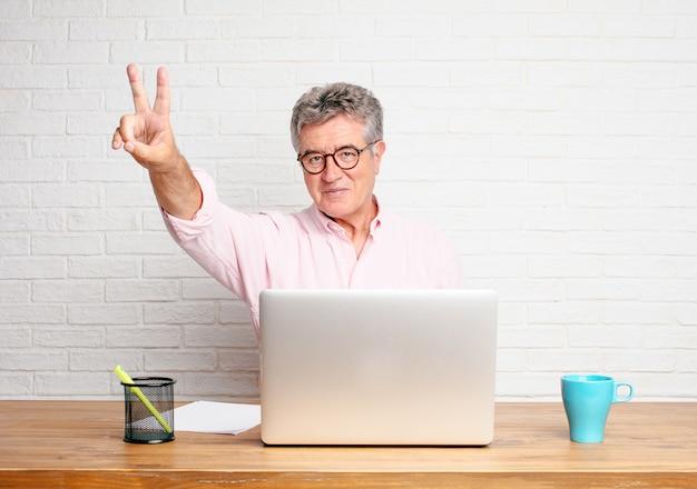 Homme d'affaires senior souriant et regardant satisfait et heureux, comptant le numéro deux avec les doigts.