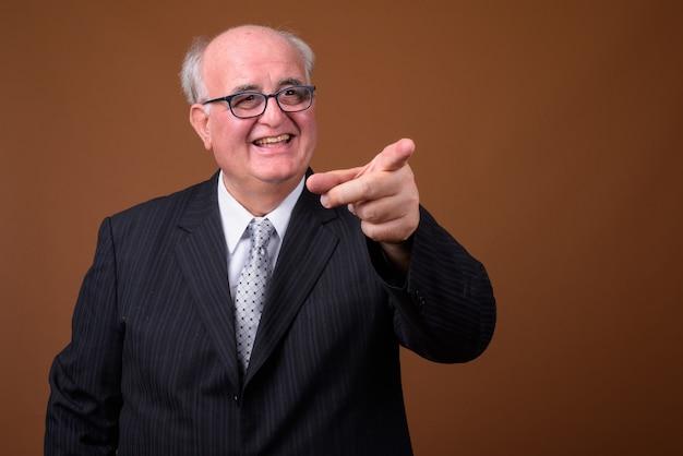 Homme d'affaires senior en surpoids portant des lunettes contre le mur marron