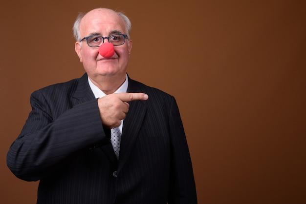 Homme d'affaires senior en surpoids portant nez de clown rouge