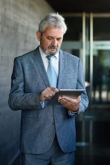 Homme d'affaires senior avec tablette informatique à l'extérieur du bâtiment de bureau moderne.