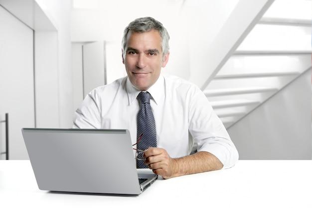 Homme d'affaires senior travaillant à l'intérieur de bureau moderne